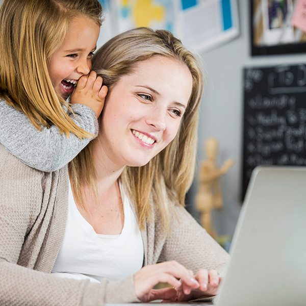 Photo of Mother working on a laptop with daughter